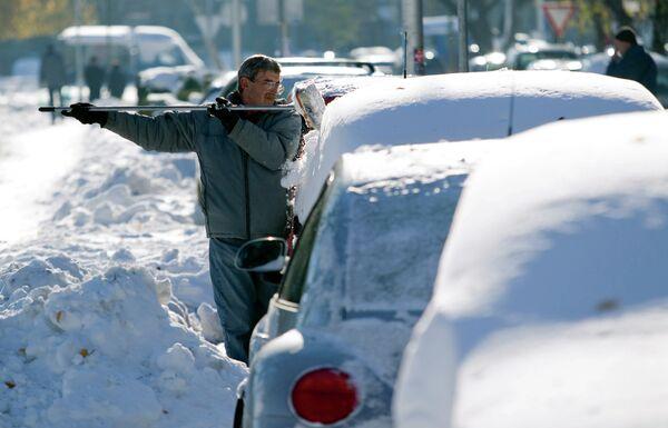 Мужчина чистит машину от снега в Загребе, Хорватия