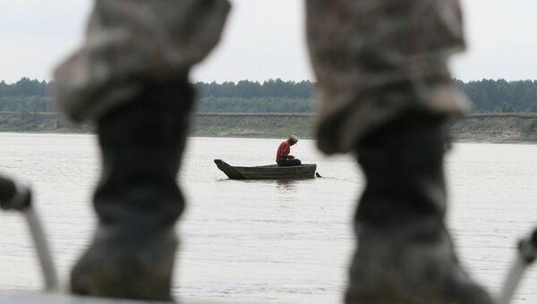 Сотрудник полиции наблюдает за браконьерской лодкой. Архивное фото