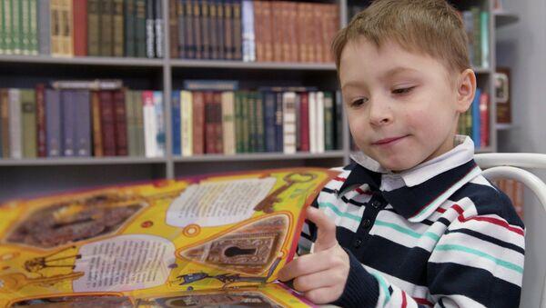 Ребенок читает книгу, архивное фото