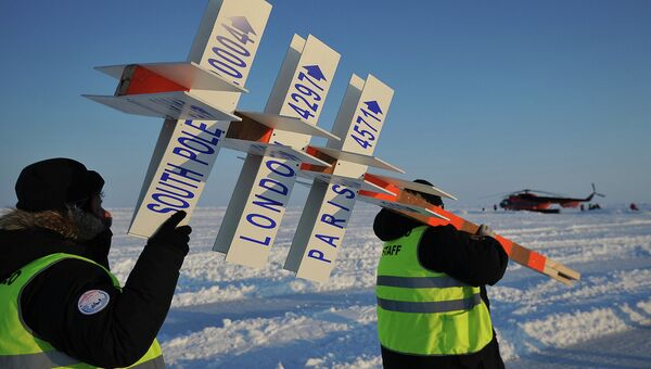 Сотрудники дрейфующей ледовой базы Барнео, находящейся в Арктике, несут символический указательный столб. Архивное фото
