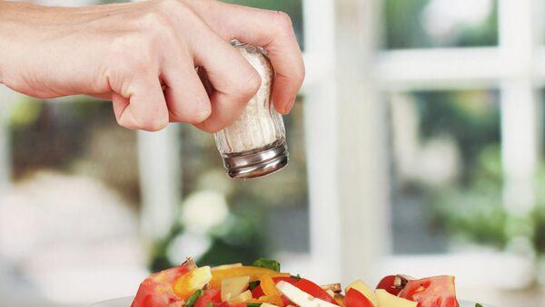 Мужчина солит салат. Архивное фото