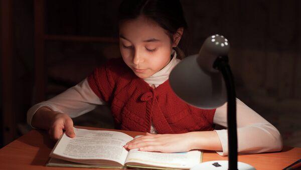 Девочка читает при свете лампы. Архивное фото