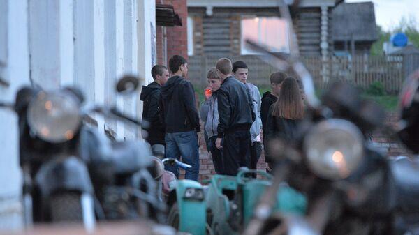 Молодые люди курят на крыльце сельского Дома культуры во время дискотеки
