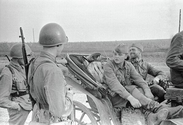 Разведчица Катя из Одессы беседует с бойцами, сидя в повозке