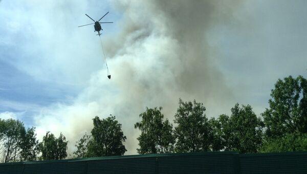 Вертолет тушит пожар на свалке в Ленинградской области