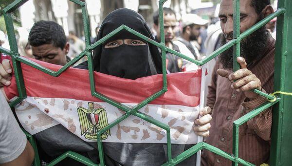 Женщина держит флаг Египта, на который кровью нанесены надписи