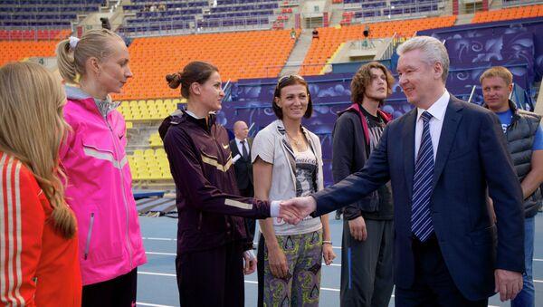 Сергей Собянин (справа на первом плане) общается с тренерами и спортсменами-легкоатлетами на стадионе Лужники