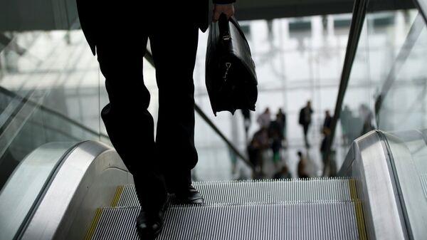 Мужчина с портфелем поднимается по эскалатору