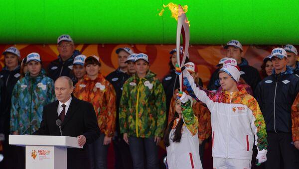 Президент РФ Владимир Путин (слева) на Красной площади во время старта эстафеты Олимпийского огня. Справа - фигуристы Лина Федорова и Максим Мирошкин.