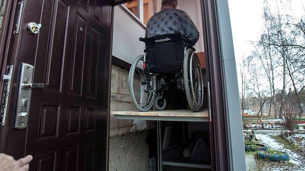 Станислав Пачгин на автоматической платформе для спуска-подъема коляски в своем подъезде