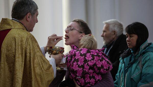 Викарий католического прихода Пресвятой Богородицы во Владивостоке отец Даниил раздает святое причастие во время Рождественской службы.
