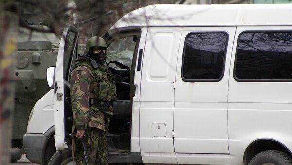 Сотрудник правоохранительных органов у автомобиля во время спецоперации по уничтожению боевиков. Архивное фото.