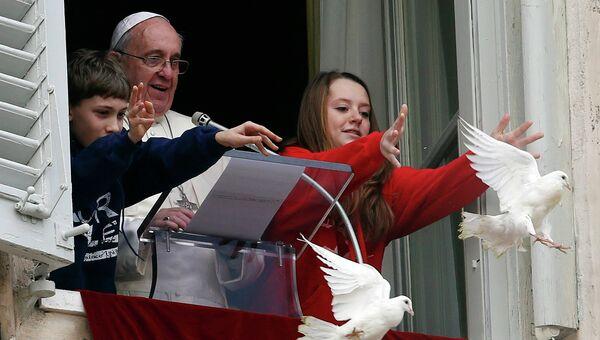 Папа Франциск вместе с двумя детьми, выпустил двух горлиц в качестве символа Мира