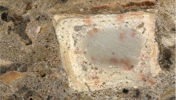 Сделанный при помощи микроскопа снимок фрагмента отложений на месте очага, где среди пепла есть обгоревшая кость и мелкие камни из почвы