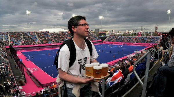 Болельщик несет пиво на трибуне стадиона перед игрой