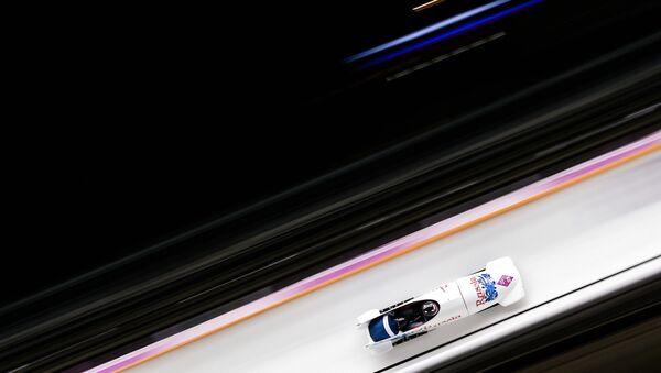 Александр Зубков и Алексей Воевода (Россия) на трассе в первом заезде двоек на соревнованиях по бобслею среди мужчин