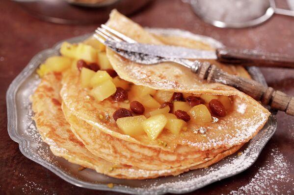 Блинчики с яблоком, медом и изюмом и орехами, посыпанные сахарной пудрой