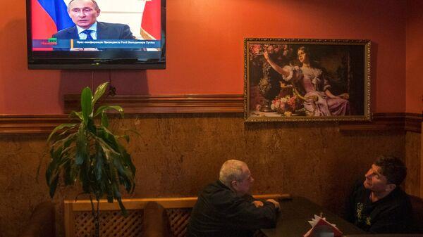 Жители Киева во время просмотра ТВ трансляции пресс-конференции президента России Владимира Путина