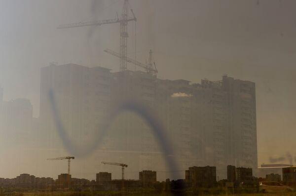 Отражение в окне строящегося жилого комплекса