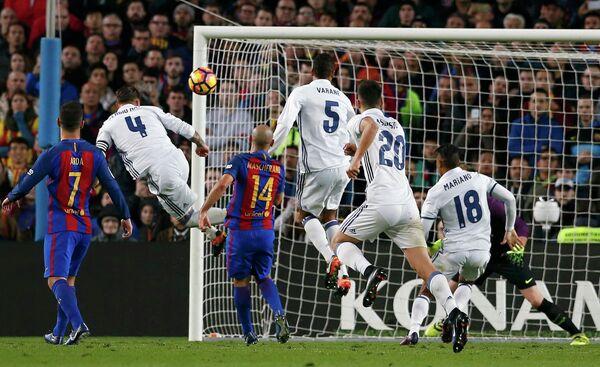 Защитник мадридского Реала Серхио Рамос (второй слева) забивает мяч в ворота голкипер Барселоны Марка-Андре Тер Штегена