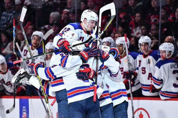 Хоккеисты сборной США радуются забитой шайбе в ворота канадцев в финальном матче молодежного чемпионата мира