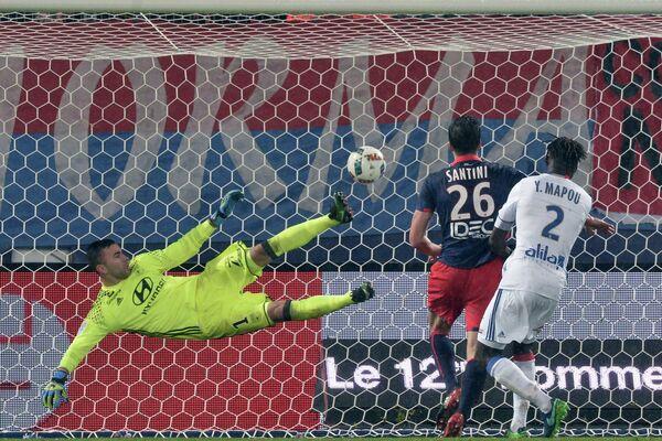 Нападающий Кана Иван Сантини (в центре) забивает мяч в ворота Лиона