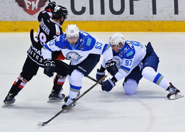 Нападающий Трактора Максим Якуценя и хоккеисты Барыса Владимир Маркелов и Кирилл Панюков (слева направо)