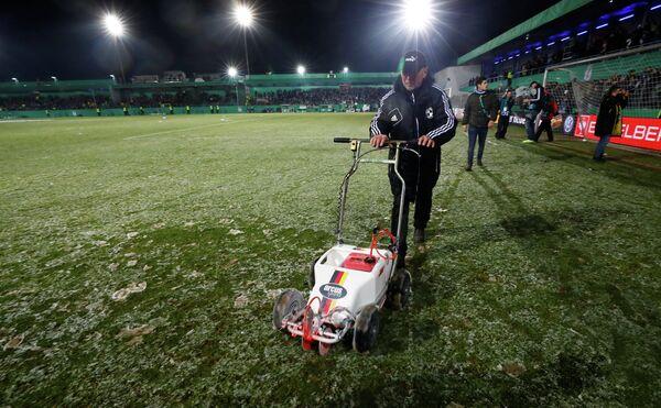 Сотрудники стадиона на поле перед отменой четвертьфинального матча Кубка Германии по футболу между Лотте и дортмундской Боруссией