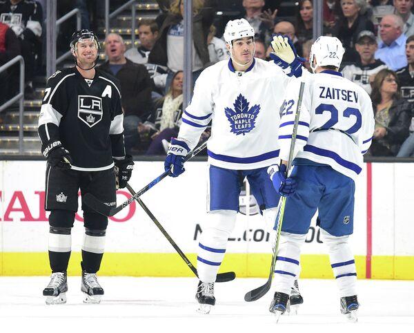 Защитник Торонто Никита Зайцев (справа) и нападающие Торонто Брайан Бойл и Лос-Анджелеса Джефф Картер