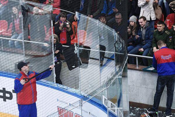 Сотрудники спортивной арены убирают осколки от разбитого стекла ограждения