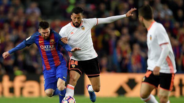 Нападающий Барселоны Лионель Месси (слева) и защитник Валенсии Эсекьель Гарай