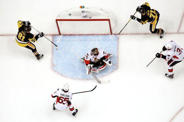 Форвард Питтсбурга Евгений Малкин (крайний справа) забрасывает шайбу в ворота голкипера Оттавы Крэйга Андерсона