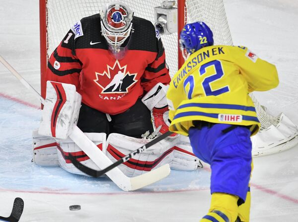Вратарь сборной Канады Кэлвин Пикар и форвард сборной Швеции Джоэль Эрикссон Эк (справа)