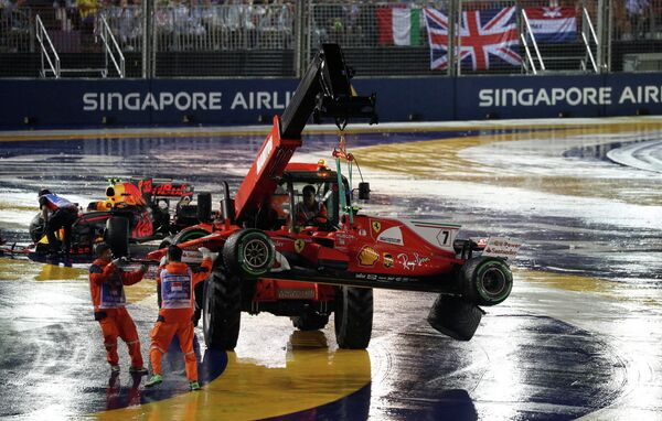 Работники автодрома на Гран-при Сингапура эвакуируют с трассы болиды гонщика Феррари Кими Райкконена (справа) и пилота Ред Булл Макса Ферстапенна