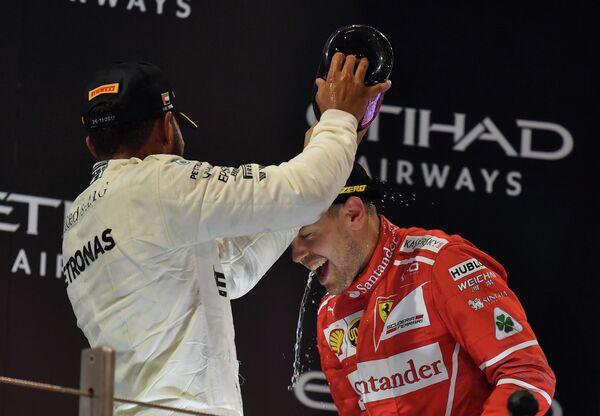 Пилот Мерседеса Льюис Хэмилтон и гонщик Феррари Себастьян Феттель (слева направо) на подиуме