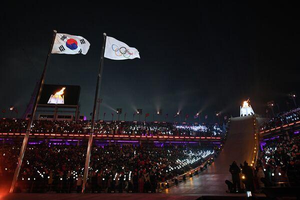 Флаги Южной Кореи - страны-хозяйки Игр, МОК (олимпийские кольца) и олимпийский огонь