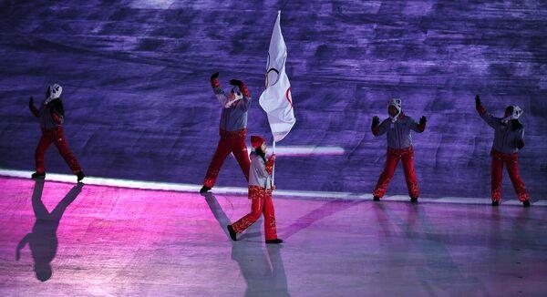 Волонтер несет олимпийский флаг, под которым на ОИ-2018 выступают атлеты из России