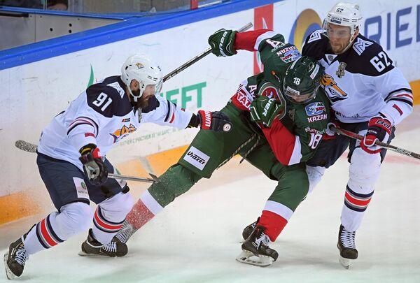 Хоккеисты Металлурга Никита Пивцакин (слева), Оскар Осала (справа) и форвард Ак Барса Ярослав Косов