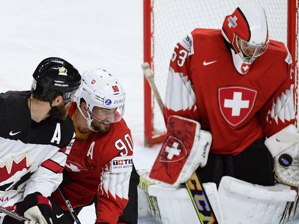 Нападающий сборной Канады Райан О'Райлли, защитник сборной Швейцарии Роман Йози и вратарь сборной Швейцарии Леонардо Дженони (слева направо)