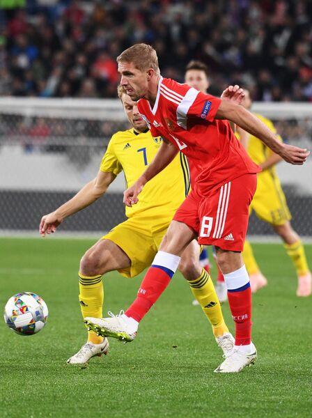 Полузащитники сборной Швеции Себастьян Ларссон и сборной России Юрий Газинский (справа)