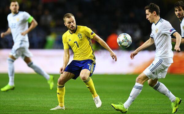 Полузащитник сборной Швеции Себастьян Ларссон и полузащитник сборной России Далер Кузяев (справа)