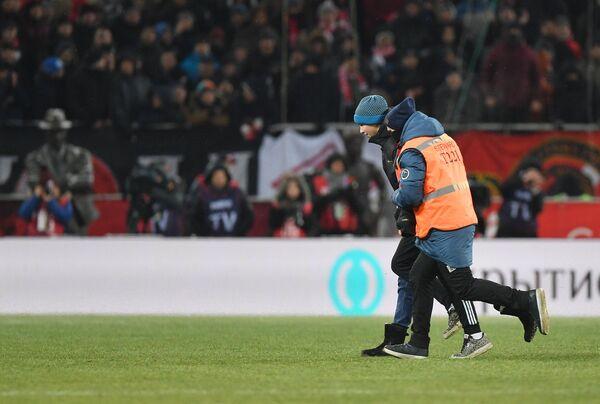 Стюарды задерживают болельщика, выбежавшего на поле