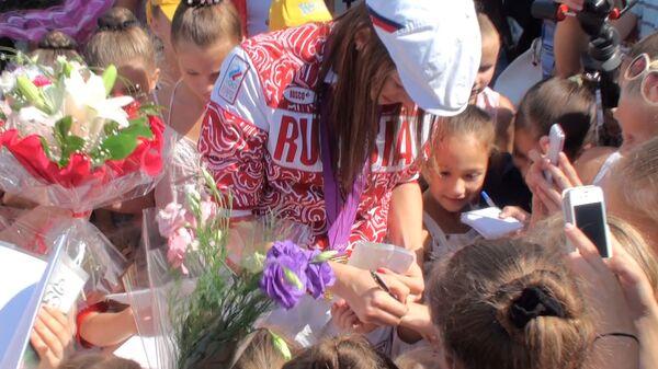 Окруженная юными гимнастками чемпионка Донскова ставит автографы на руках