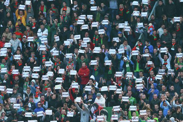 Болельщики Локомотива держат в руках листы бумаги с напдисью Увольняй!