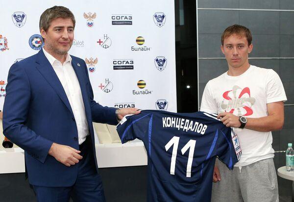 Генеральный директор ФК Волга Сергей Анисимов (слева) вручает дебютанту футбольного клуба Роману Концедалову
