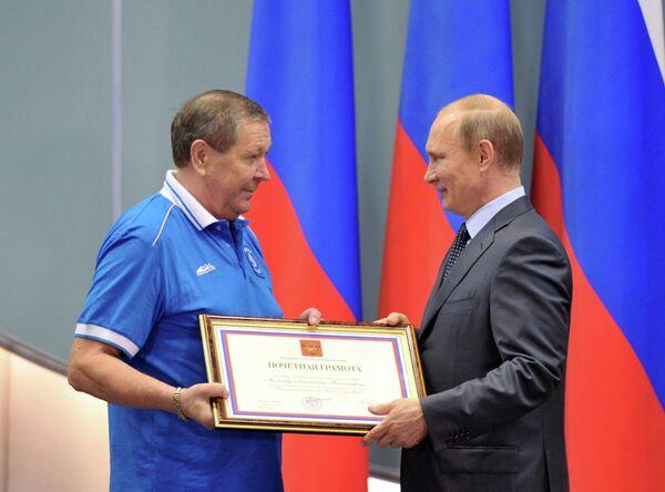 Президент России Владимир Путин (справа) вручает почетную грамоту советнику президента клуба Динамо Александру Мальцеву