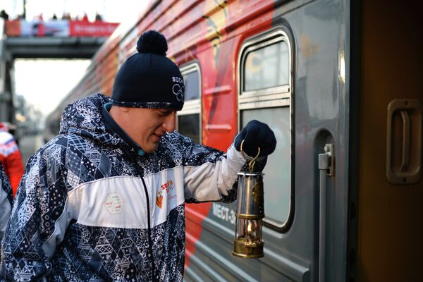 Хранитель огня заходит в железнодорожный вагон с лампадой олимпийского огня