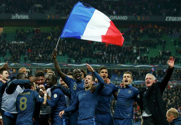Футболисты сборной Франции вместе с главным тренером Дидье Дешамом радуются после победы над украинцами и выхода на чемпионат мира 2014 года