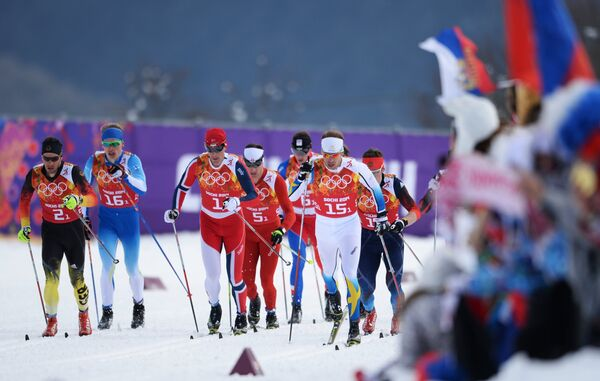 Спортсмены на дистанции финального забега командного спринта в соревнованиях по лыжным гонкам