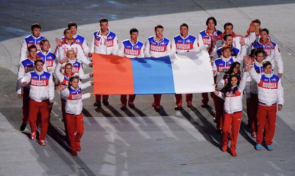 Российские медалисты выносят российский флаг во время церемонии закрытия XXII зимних Олимпийских игр в Сочи